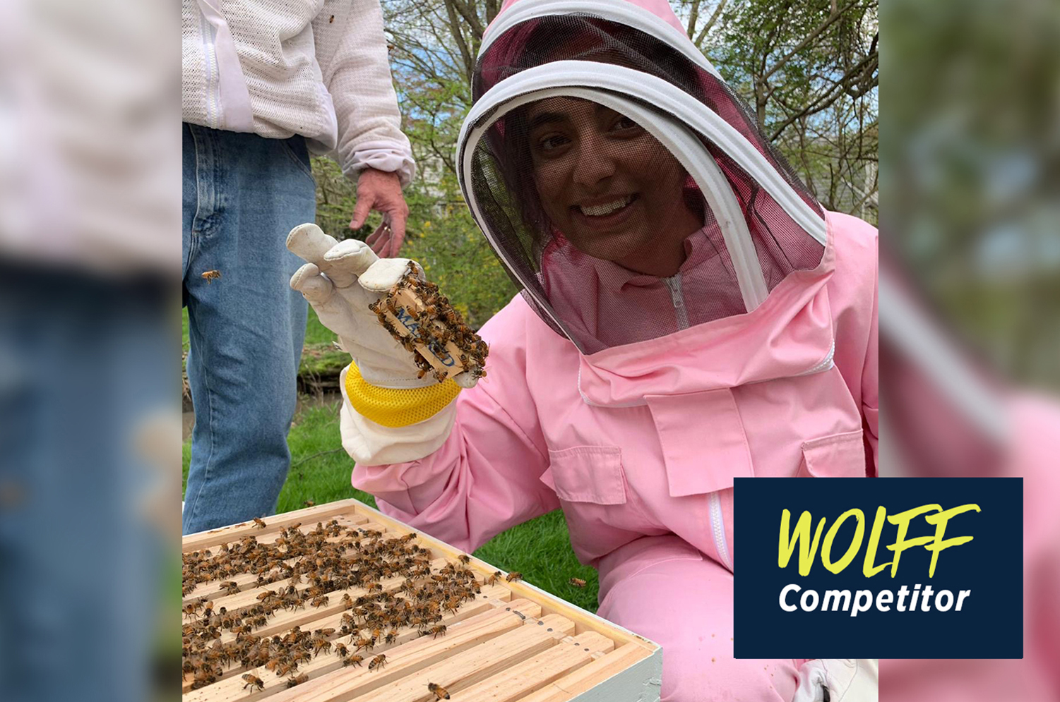 Raina Jain in beekeeping suit next to hive bodies for bees